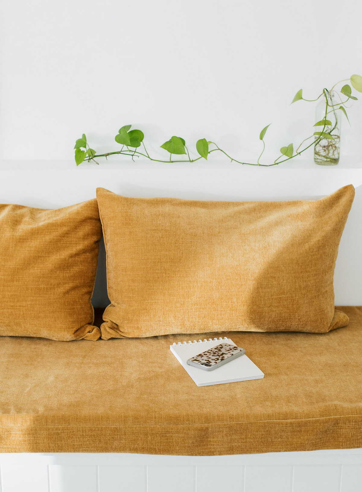 Notebook and phone on mustard sofa